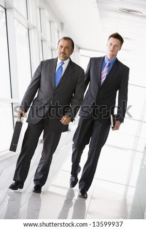 Two businessman walking through office lobby