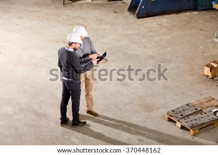 Two businessman working in factory.