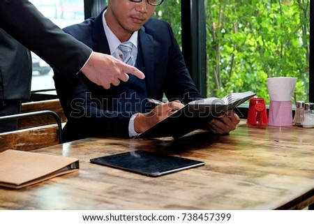 Two businessman working on tablet, partner discuss plan or idea and opinion meeting, Asian bussinessman are discussing their working on a wood table beside window at coffee shop during breaking time #738457399