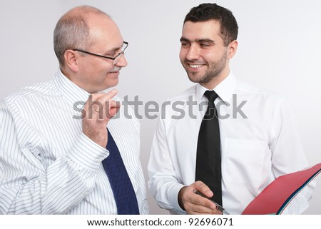 Two businessman, young and mature one discuss something.
