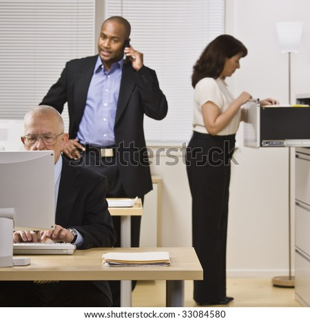 Two businessmen and woman are working in an office. The elderly man is on a computer, the younger is on a cell phone and the woman in looking through a filing cabinet.  Square shot.