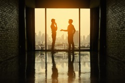 Two businessmen are negotiating business in office on the building. Two businessmen business negotiations.(Silhouette)