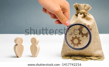 Two businessmen are standing near the bag with the image of gears. The process of learning a new employee. Share experience and knowledge. Adjustment of business processes and optimization.