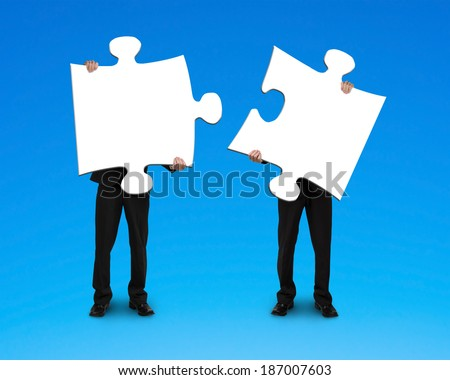 Two businessmen assembling puzzles blue background Stock photo ©