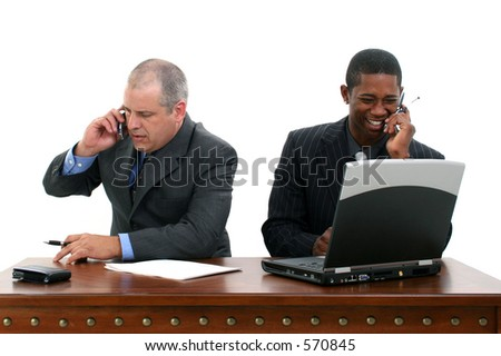 Two businessmen at desk each in conversation on cellphone.  Shot in studio over white.