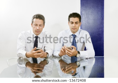 Two businessmen checking blackberries in meeting room.