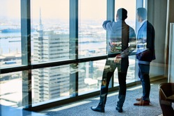Two businessmen deep in discussion together while standing by windows high up in an office tower overlooking the city