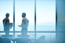Two businessmen deep in discussion together while standing in an office boardroom with windows overlooking the ocean and city