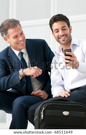Two businessmen discussing together on a news on a smart phone during a business travel