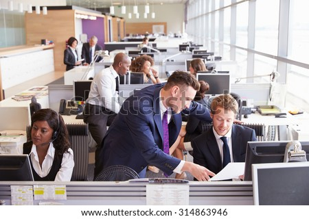 Two businessmen discussing work in a busy, open plan office