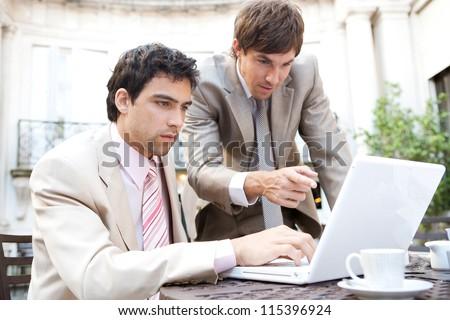 Two businessmen focused on having a meeting while sitting in a classic coffee shop terrace, using a laptop computer.