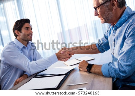 Two businessmen giving a handshake in the office