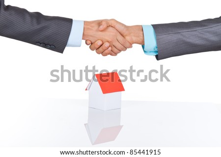Two businessmen hands in elegant suits handshake, miniature house, isolated on white background, with empty copy space