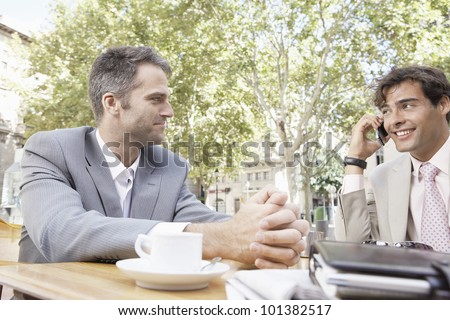 Two businessmen having a meeting in a coffee shop's terrace in the city, outdoors.