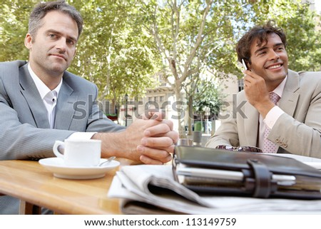 Two businessmen having a meeting in a coffee shop terrace outdoors.