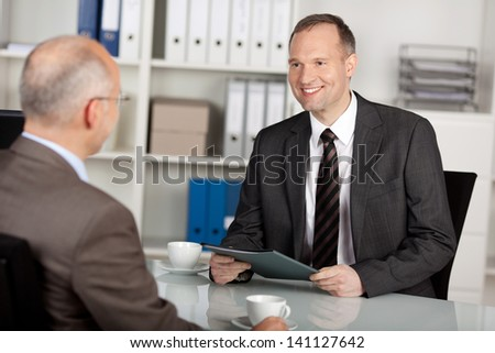 Two businessmen having conversation inside the office