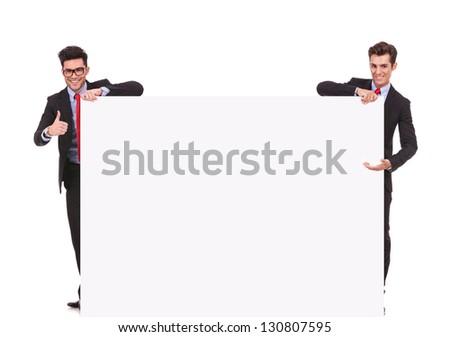 two businessmen holding a big blank sign , one presenting and one making the ok thumbs up gesture