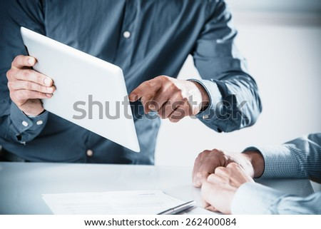 Two businessmen in a meeting discussing a projet on a tablet computer pointing to the screen, close up of their hands