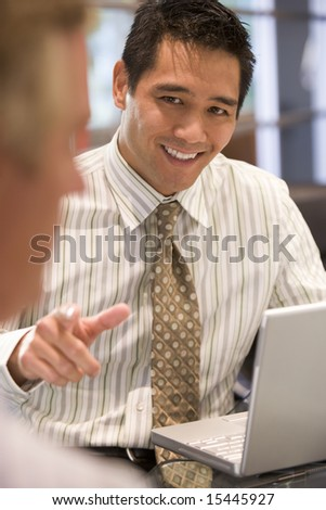 Two businessmen in boardroom with laptop talking