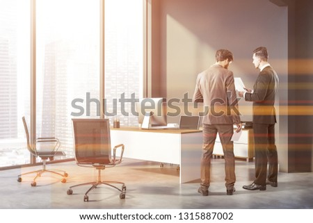 Two businessmen in corner of manager office with gray walls, concrete floor, panoramic window, white and wooden computer table, black chair and two chairs for visitors. Toned image #1315887002