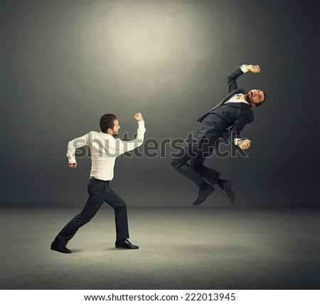 two businessmen in fight. one man standing and hitting, second man flying and screaming. photo in the dark room