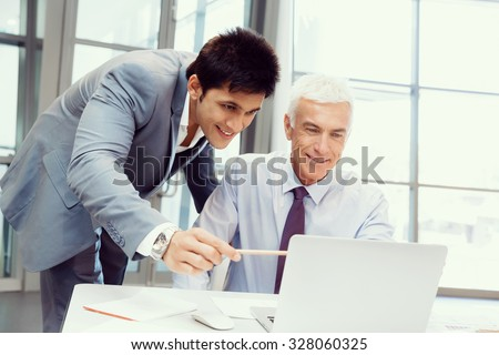 Two businessmen in fornt of computer in office