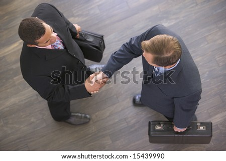 Two businessmen indoors shaking hands - stock photo