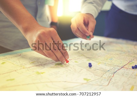 Two businessmen is pointing at the map with the pins in business meeting. They are brainstorming about the target of customer in terms of marketing.