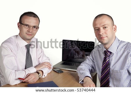 Two businessmen looking at camera with laptop behind