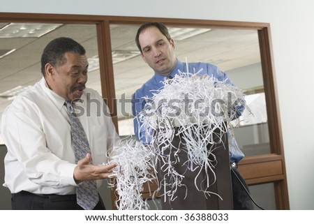 Two businessmen looking at shredded papers