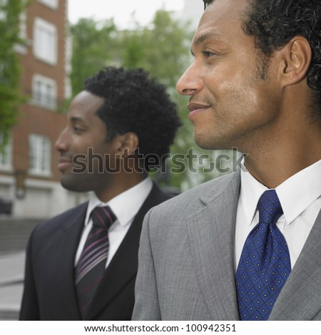 Two businessmen looking to side outdoors