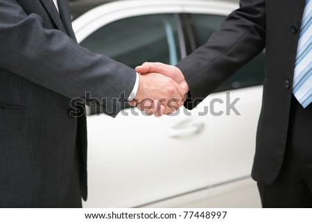 two businessmen making handshake with a luxury car at the back