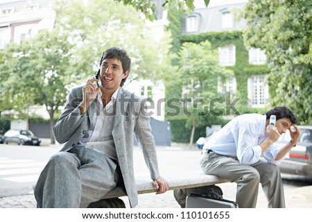 Two businessmen making phone calls on their cells while sitting on a bench in the financial district of the city.