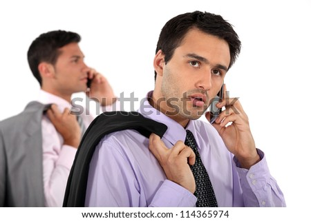 Two businessmen making telephone calls