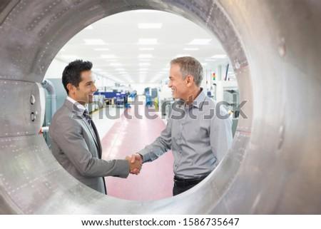 Two Businessmen Meeting In Engineering Factory In Factory
