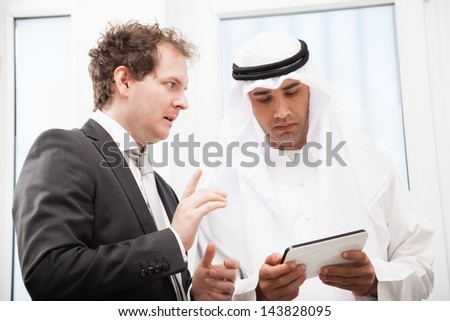 Two businessmen people working and discussing using digital tablet