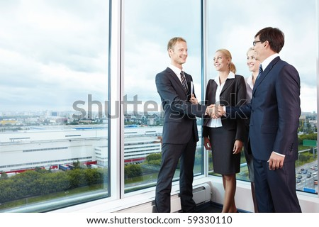 Two businessmen shake hands next to business women