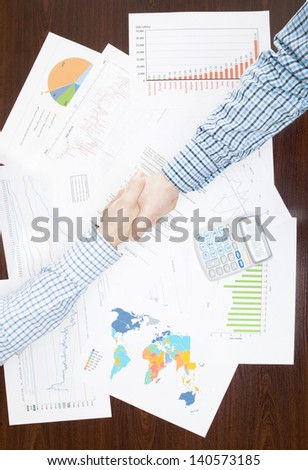 Two businessmen shaking hands above the desk - stock photo