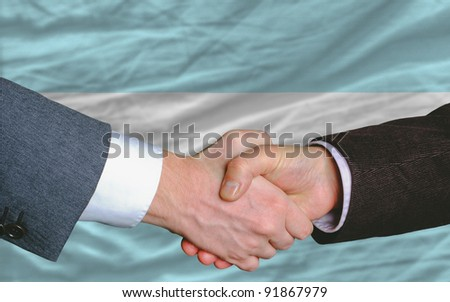 two businessmen shaking hands after good business investment  agreement in argentina, in front of flag
