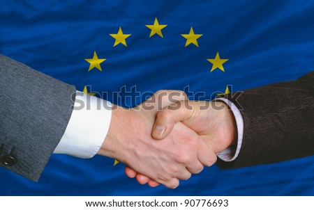 two businessmen shaking hands after good business investment  agreement in europe, in front of flag