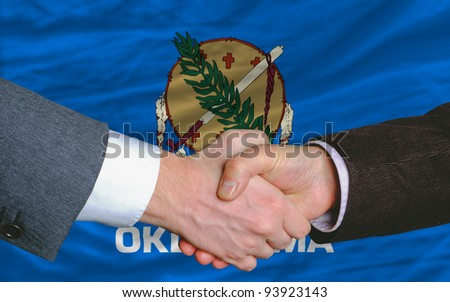 two businessmen shaking hands after good business investment agreement in front US state flag of oklahoma