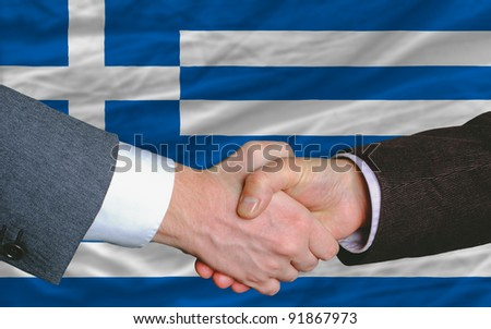 two businessmen shaking hands after good business investment  agreement in greece, in front of flag