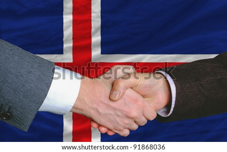 two businessmen shaking hands after good business investment  agreement in iceland, in front of flag