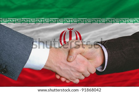 two businessmen shaking hands after good business investment  agreement in iran, in front of flag