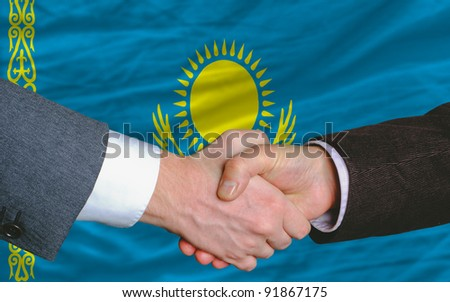 two businessmen shaking hands after good business investment  agreement in kazakhstan, in front of flag