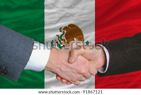 two businessmen shaking hands after good business investment  agreement in mexico, in front of flag
