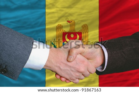 two businessmen shaking hands after good business investment  agreement in moldova, in front of flag