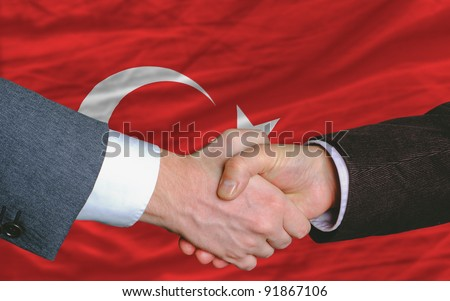 two businessmen shaking hands after good business investment  agreement in turkey, in front of flag