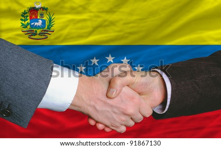 two businessmen shaking hands after good business investment  agreement in venezuela, in front of flag