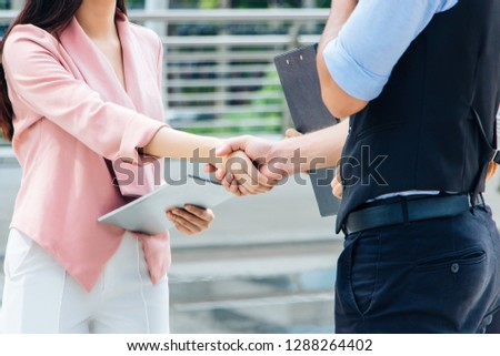 Two businessmen shaking hands after reaching an agreement. The business has a middleman stand.Everyone is smiling and Happy. At the center of Bangkok, Thailand A backdrop of skyscrapers and buildings.